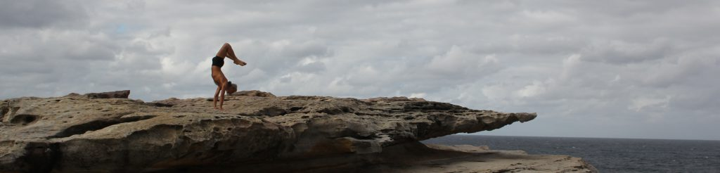 Simon Borg-Olivier. Ardho Mukha Vrksasana in a Clovelly Cliff Storm, by Stuart Fell